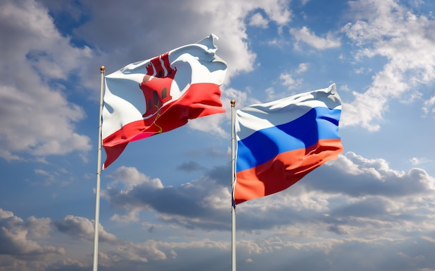 Schöne nationalstaatsflaggen von gibraltar und von russland zusammen auf blauem himmel. 3d-grafik