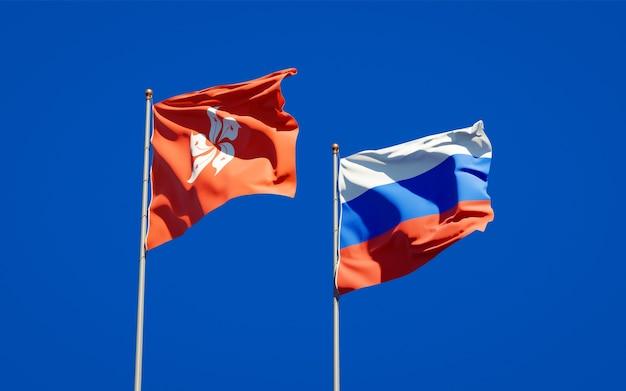 Schöne nationalstaatsflaggen von hong kong hk und von russland zusammen auf blauem himmel. 3d-grafik