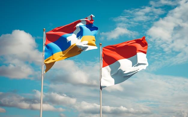 Schöne nationalstaatsflaggen von indonesien und von artsakh zusammen auf blauem himmel