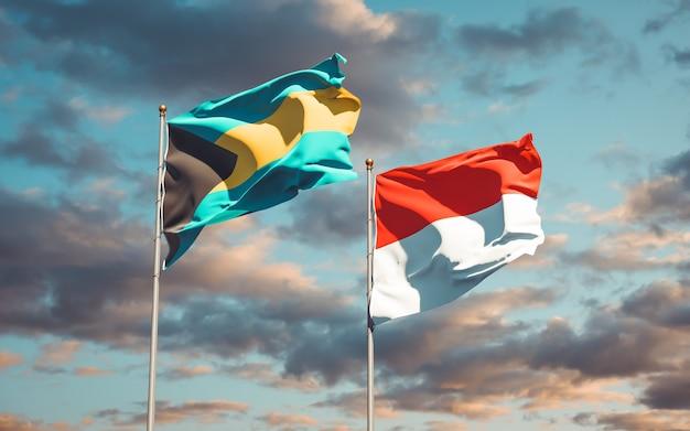 Schöne nationalstaatsflaggen von indonesien und von bahamas zusammen auf blauem himmel
