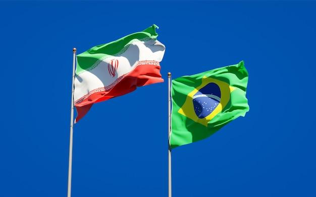 Schöne nationalstaatsflaggen von iran und brasilien zusammen auf blauem himmel