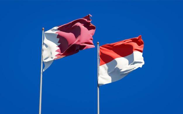 Schöne nationalstaatsflaggen von katar und indonesien zusammen auf blauem himmel