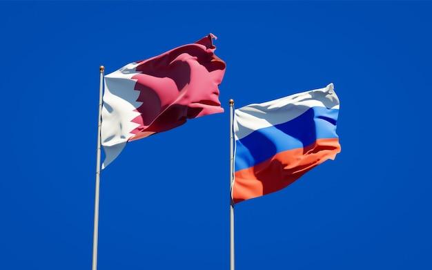 Schöne nationalstaatsflaggen von katar und russland zusammen auf blauem himmel. 3d-grafik