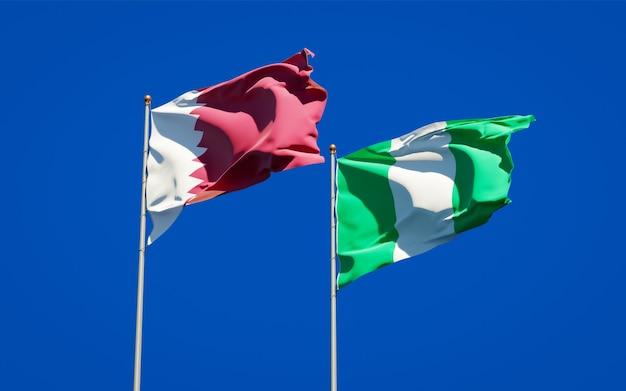 Schöne nationalstaatsflaggen von katar und von nigeria zusammen auf blauem himmel