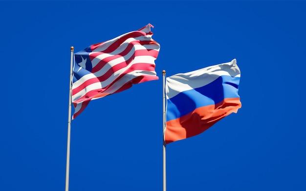 Schöne nationalstaatsflaggen von liberia und von russland zusammen auf blauem himmel. 3d-grafik
