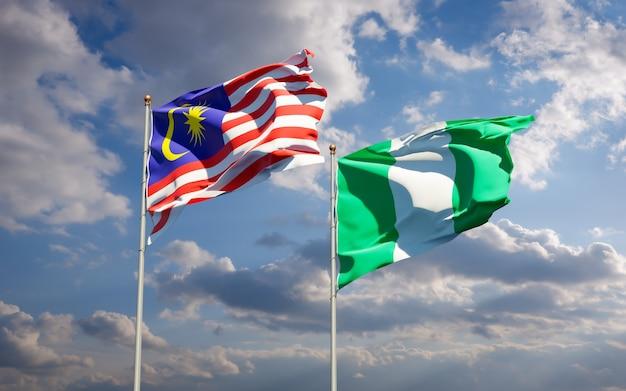 Schöne nationalstaatsflaggen von malaysia und von nigeria zusammen auf blauem himmel