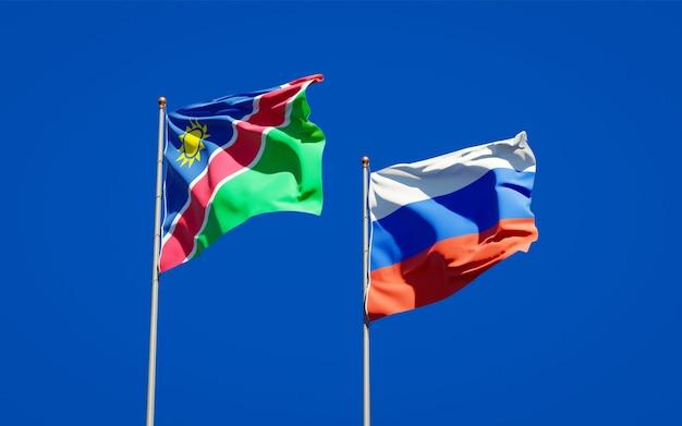 Schöne nationalstaatsflaggen von namibia und russland zusammen auf blauem himmel. 3d-grafik