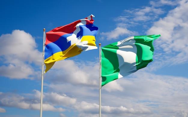 Schöne nationalstaatsflaggen von nigeria und von artsakh zusammen auf blauem himmel