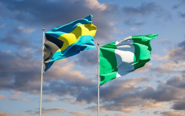 Schöne nationalstaatsflaggen von nigeria und von bahamas zusammen auf blauem himmel