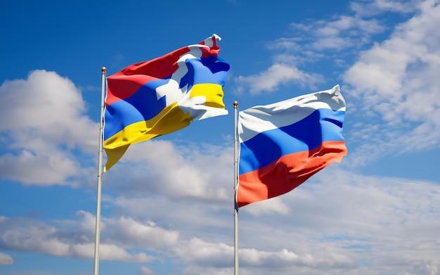 Schöne nationalstaatsflaggen von russland und von artsakh zusammen auf blauem himmel. 3d-grafik