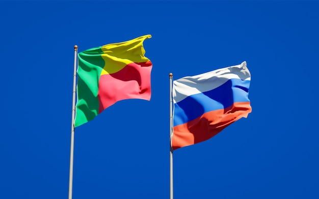 Schöne nationalstaatsflaggen von russland und von benin zusammen auf blauem himmel. 3d-grafik