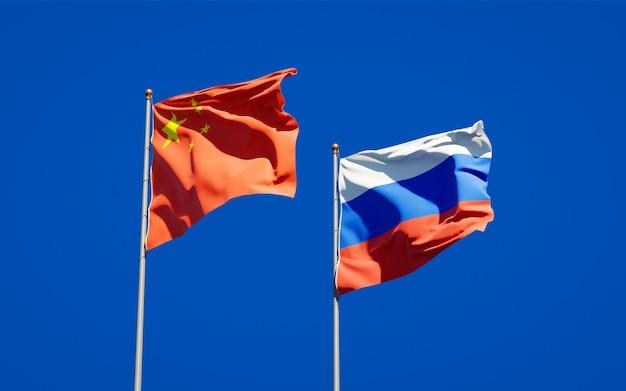 Schöne nationalstaatsflaggen von russland und von china zusammen auf blauem himmel. 3d-grafik