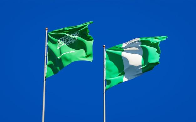 Schöne nationalstaatsflaggen von saudi-arabien und nigeria zusammen auf blauem himmel