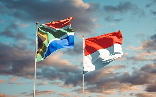 Schöne nationalstaatsflaggen von südafrika und indonesien zusammen auf blauem himmel