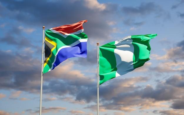Schöne nationalstaatsflaggen von südafrika und von nigeria zusammen auf blauem himmel