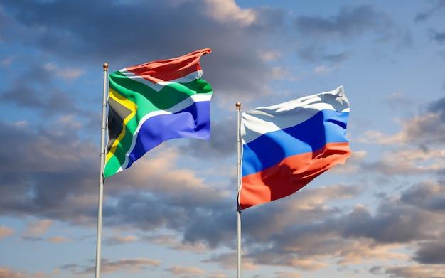 Schöne nationalstaatsflaggen von südafrika und von russland zusammen auf blauem himmel. 3d-grafik