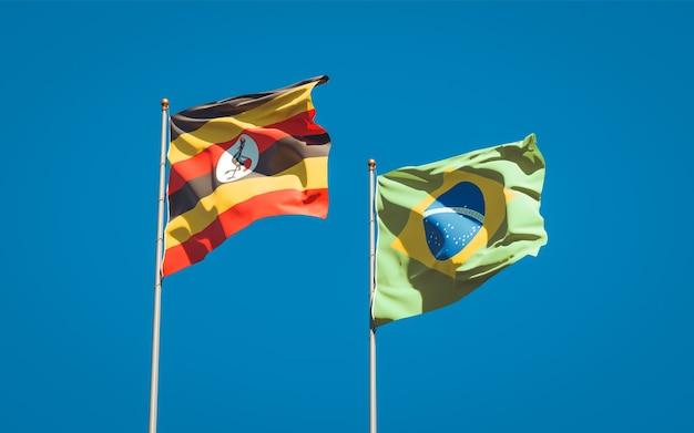 Schöne nationalstaatsflaggen von uganda und brasilien zusammen auf blauem himmel