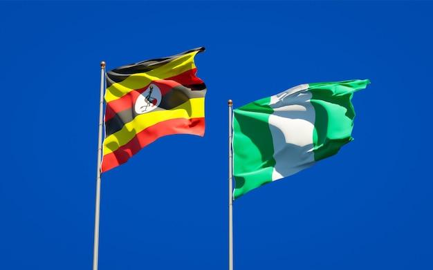 Schöne nationalstaatsflaggen von uganda und nigeria zusammen auf blauem himmel