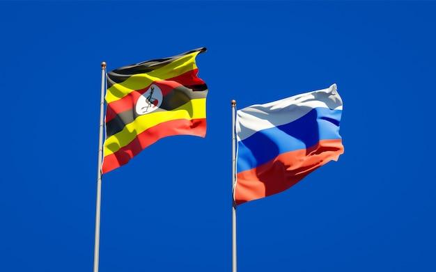 Schöne nationalstaatsflaggen von uganda und russland zusammen auf blauem himmel. 3d-grafik