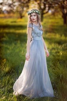 Schöne natürliche frau im blühenden garten
