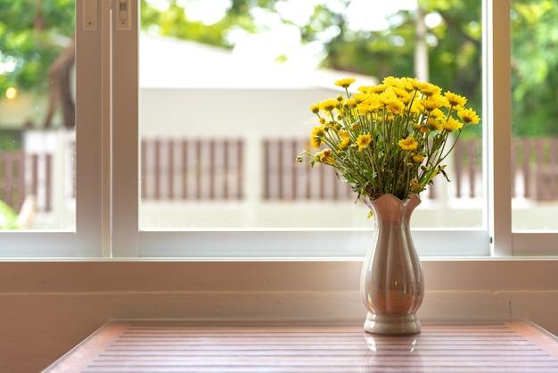 Schöne natürliche gelbe blumen im vase setzten sich auf dem tisch mit licht vom fenster.