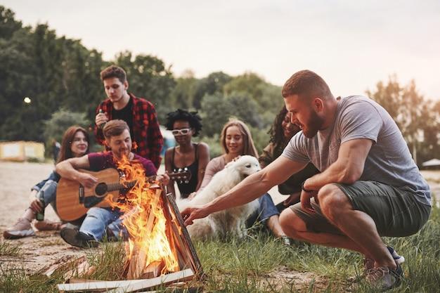 Schöne natur. eine gruppe von menschen hat ein picknick am strand. freunde haben spaß am wochenende.