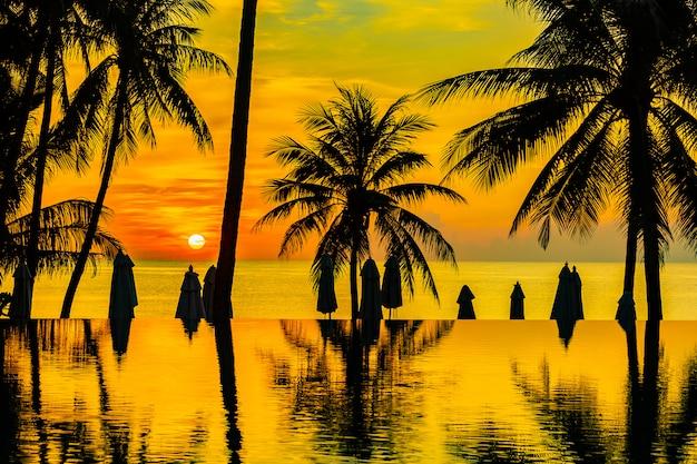 Schöne naturlandschaft im freien mit seeozean- und kokosnusspalme um swimmingpool bei sunrsie oder sonnenuntergang