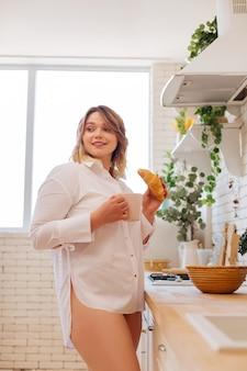 Schöne nette frau, die in der küche steht, während sie kaffee mit einem croissant trinkt