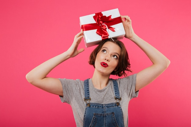 Schöne nette junge frau, die geschenkbox hält.
