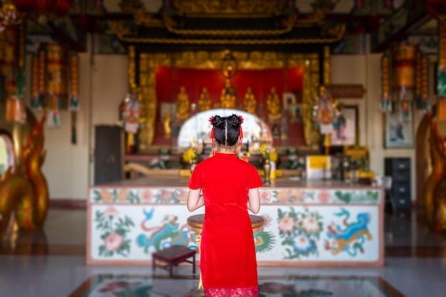 Schöne nette kleine asiatische junge frau, die rotes traditionelles chinesisches cheongsam trägt