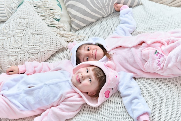 Schöne nette mädchen, die auf bett in den lustigen pyjamas aufwerfen
