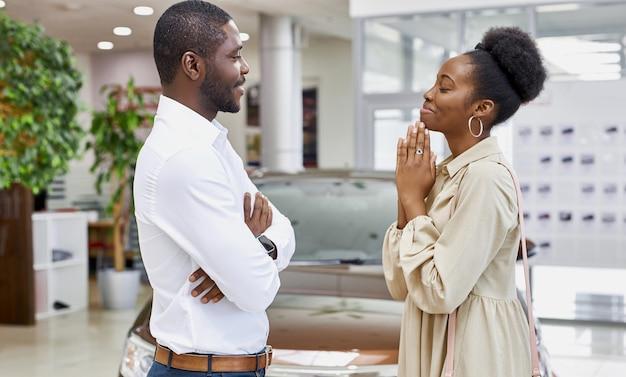 Schöne niedliche afrikanische frau, die ihren ehemann im autoausstellungsraum bettelt