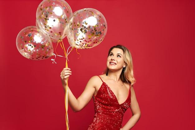 Schöne noble junge frau, die das rote kleid des niedrigen halses trägt, das ballons aufwirft und hält