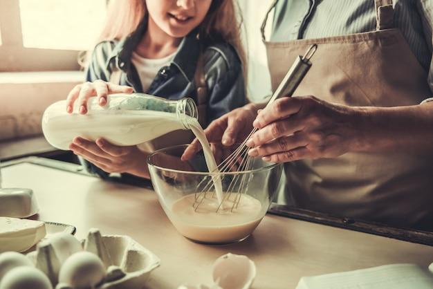 Schöne oma und enkelin schlagen eier.