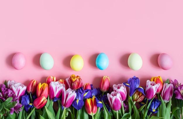 Schöne ostergrenze mit frühlingsblumen und eiern auf einem rosa hintergrund. osterblumenhintergrund. kopieren sie platz, draufsicht, flache lage. platz für text.