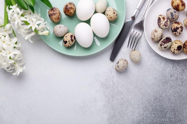 Schöne ostern tischdekoration. grüner minzteller, eier, hyazinthe und silberbesteck auf steinhintergrund. leerzeichen kopieren - bild