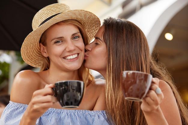 Schöne paar lesbische frauen trinken kaffee in der cafeteria im freien, genießen zusammengehörigkeit, küssen sich, haben ein breites lächeln. schöne frau glücklich, kuss von freundin zu erhalten. gegenseitige liebe.