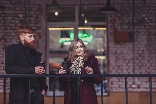 Schöne paar leute in warmer winterkleidung mit tassen kaffee