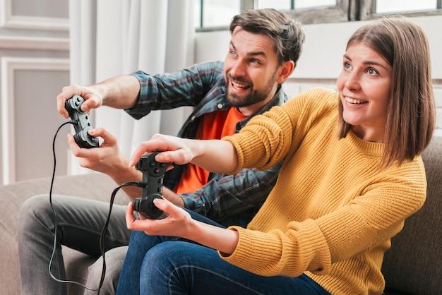 Schöne paare, die videospiele auf konsole spielen