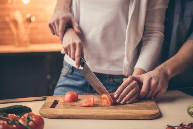 Schöne paare, die zusammen in der küche kochen