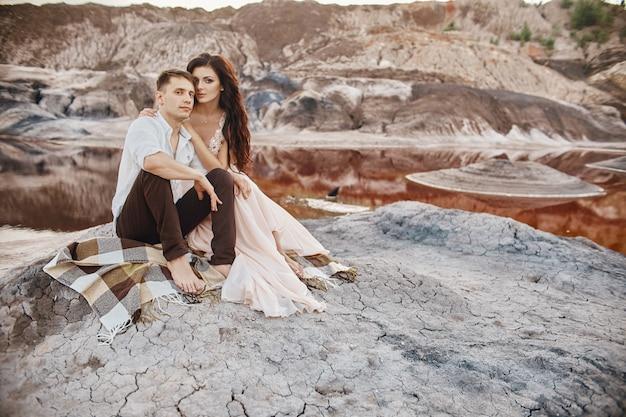 Schöne paare in der liebe, die das sitzen auf den felsen inmitten der fabelhaften berge küsst und umarmt. roter blutsee. ein mann und eine frau in einem schönen hochzeitskleid. langes helles sommerkleid auf einem frauenkörper