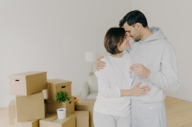Schöne paare umarmen sich und fühlen sich glücklich, halten schlüssel vom neuen modernen ersten haus, ziehen in wohnung für das zusammenleben um, werfen in leerem raum mit verpackten kartonkästen auf, fühlen liebe miteinander. grundeigentum