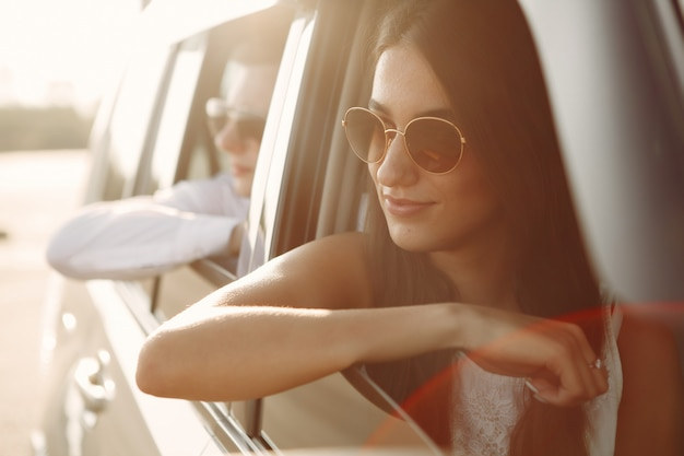 Schöne paare verbringen zeit in einem sommerpark, der in einem auto sitzt