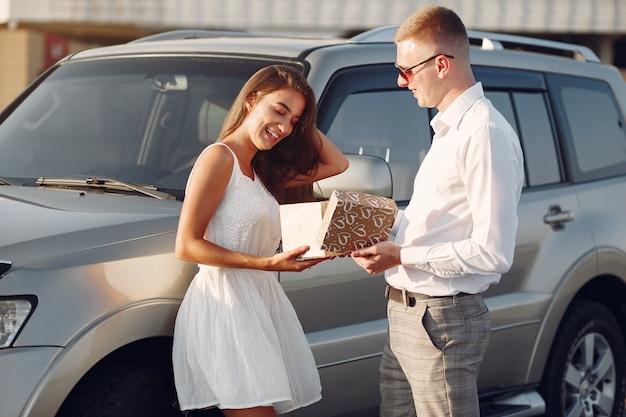 Schöne paare verbringen zeit in einem sommerpark nahe einem auto