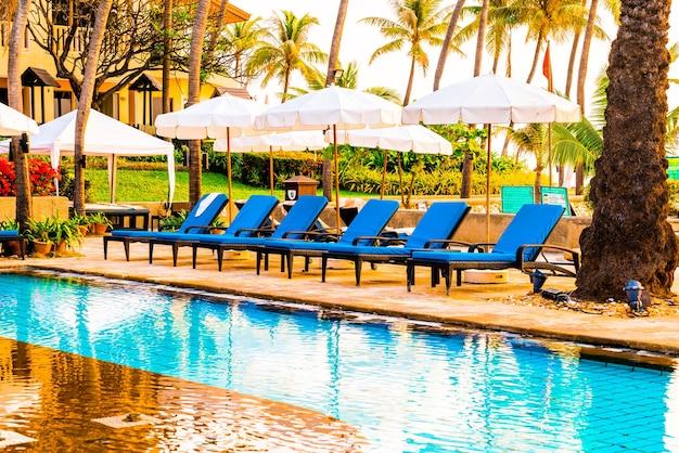 Schöne palme mit sonnenschirm stuhl pool im luxushotel resort zu sonnenaufgang zeiten, urlaub und urlaubskonzept