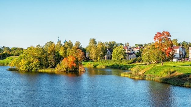 Schöne panorama-herbstlandschaft mit hellen bäumen am seeufer.