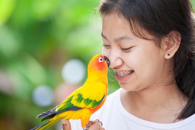 Schöne papageienvögel, die auf frauenhand stehen. asiatisches jugendlichmädchenspiel mit ihrem haustierpapageienvogel
