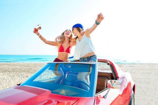 Schöne party-girls tanzen in einem auto am strand