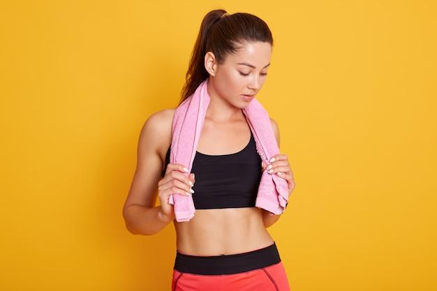 Schöne passende frau, die im fitnessstudio mit ihrem rosa handtuch um ihre schultern aufwirft, während sie sich darauf vorbereitet, ihr training zu beginnen