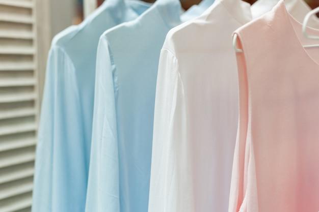 Schöne pastellfarbene kleidung auf dem kleiderbügel